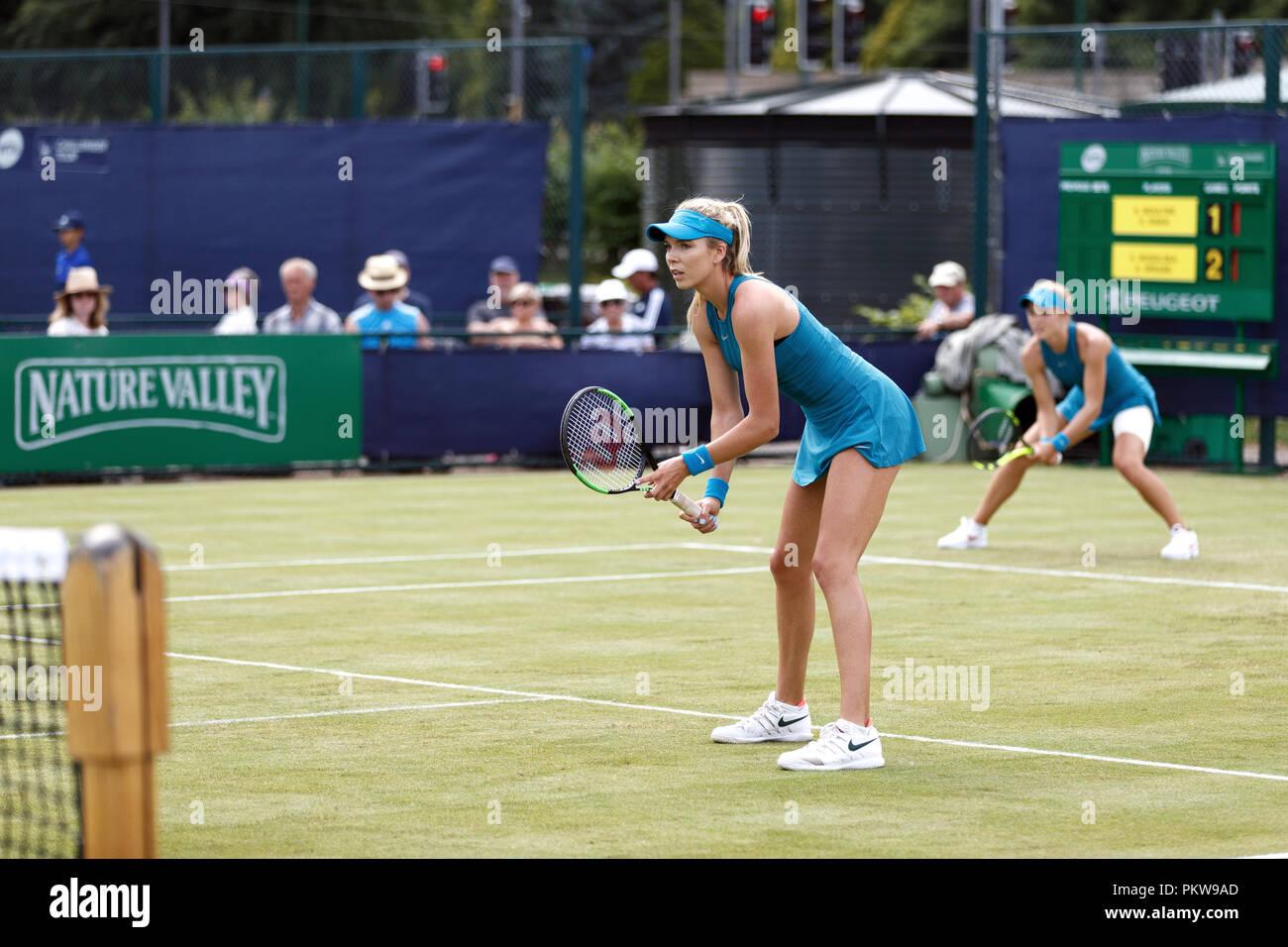 Jugadores de tenis británica Katie Boulter (primer plano) y Katie Swan (fondo) a la espera de su oponente sirven durante un partido de dobles femenino en un torneo profesional de corte de césped en el Reino Unido. Boulter y Swan jugaron juntos en la adecuación de los trajes. Foto de stock