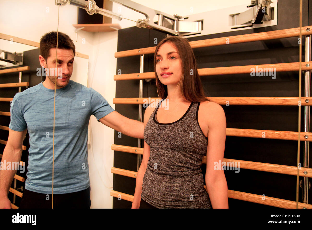 Mujer joven ejercicio en un gimnasio con la ayuda de su entrenador personal en tecnología kinesis correas de máquina en el gimnasio. Deporte, fitness Imagen De Stock