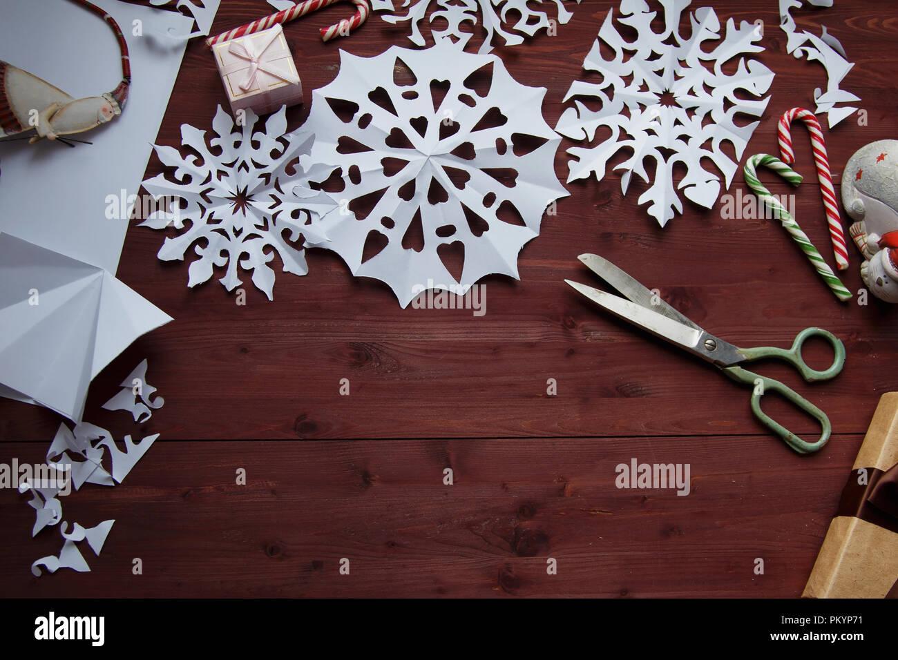 Concepto de Año Nuevo. Los copos de nieve de papel cortado, regalos, tijeras en una mesa de madera espacio de copia Imagen De Stock