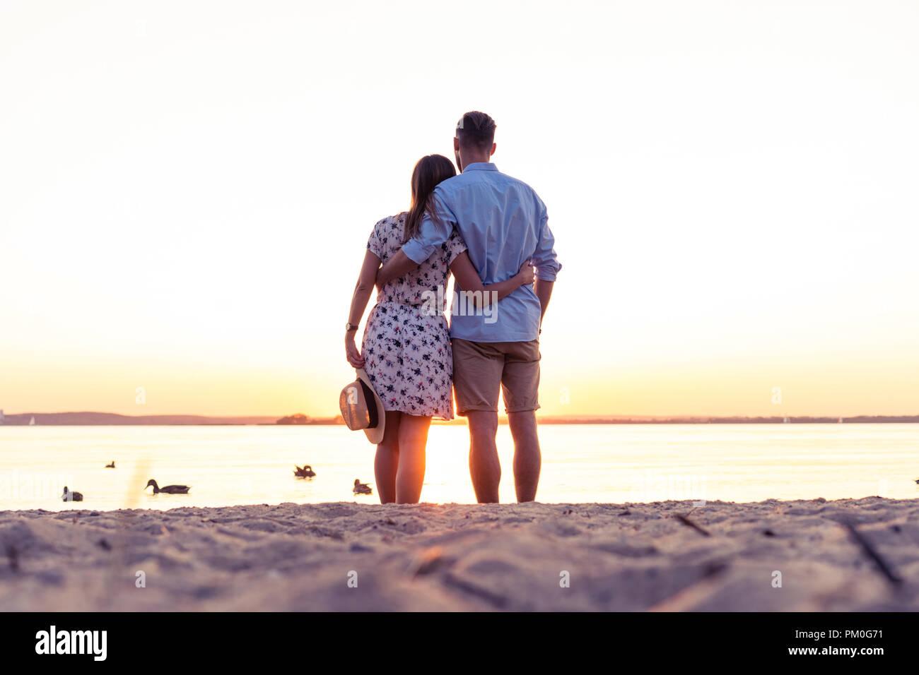 Pareja caminando por la playa al atardecer Imagen De Stock