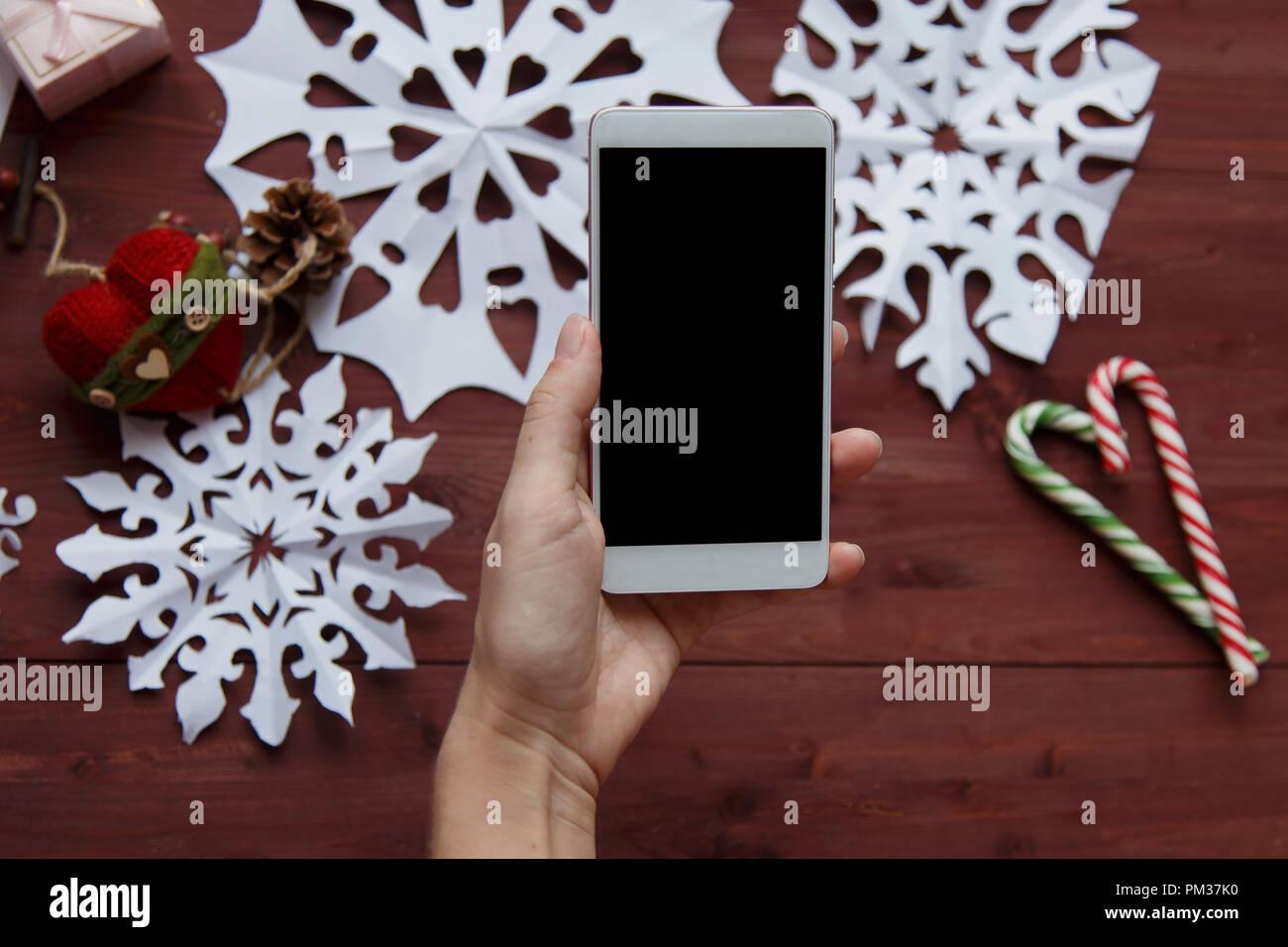 Concepto de Año Nuevo. Una mujer está haciendo una foto para un blog. Manos de mujer mantenga un smartphone, fotografiar copos de nieve de papel cortado, regalos, tijeras con un Imagen De Stock