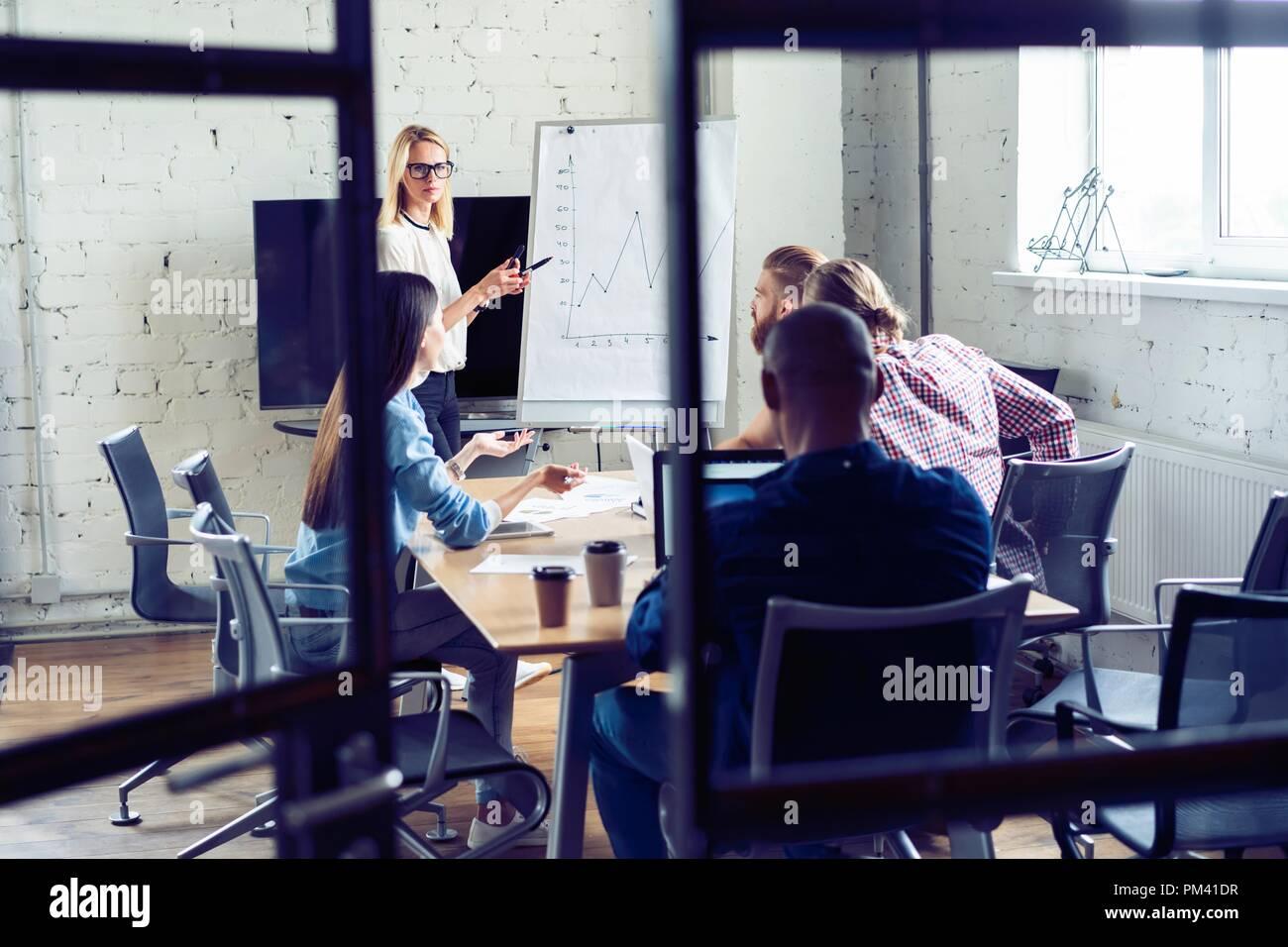 Trabajando duro para ganar. La empresaria realizando una presentación de negocio utilizando la cartelera mientras trabajaba en la oficina creativa. Imagen De Stock