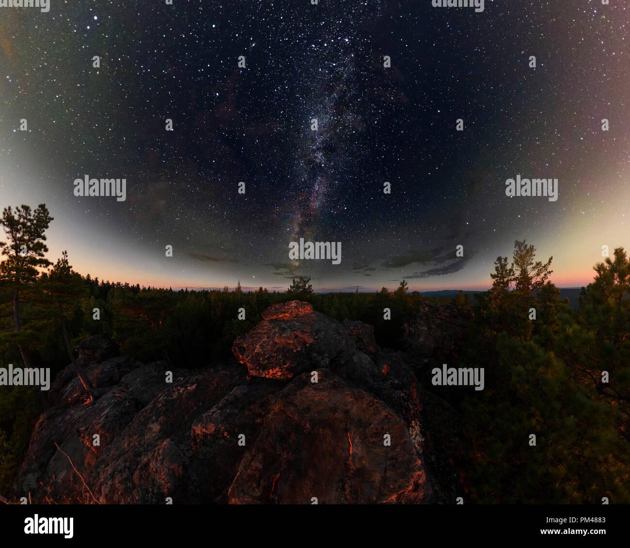 Amanecer en el bosque bajo el cielo estrellado de una vía láctea. Panorama. Foto de stock