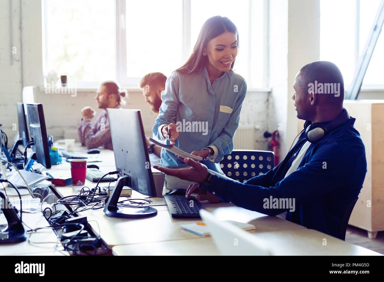 Intensa jornada de trabajo. Vista superior de los jóvenes la gente moderna en smart ropa casual hablando de negocios mientras está sentado en la oficina creativa. Imagen De Stock