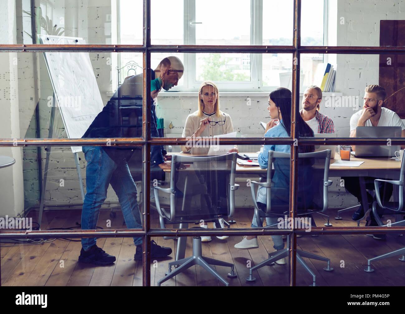 Grupo de jóvenes profesionales. Grupo de jóvenes de la gente moderna en smart ropa casual tras una reunión brainstorm estando de pie detrás de la pared de vidrio en la oficina creativa. Imagen De Stock