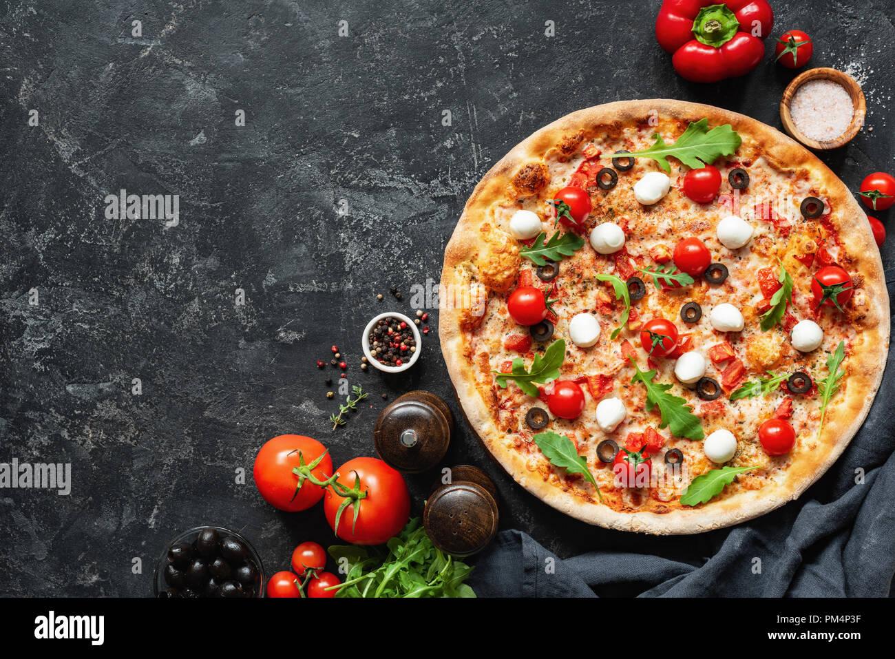La pizza italiana en negro de fondo concreta. Espacio para copiar texto. Deliciosa Pizza Imagen De Stock