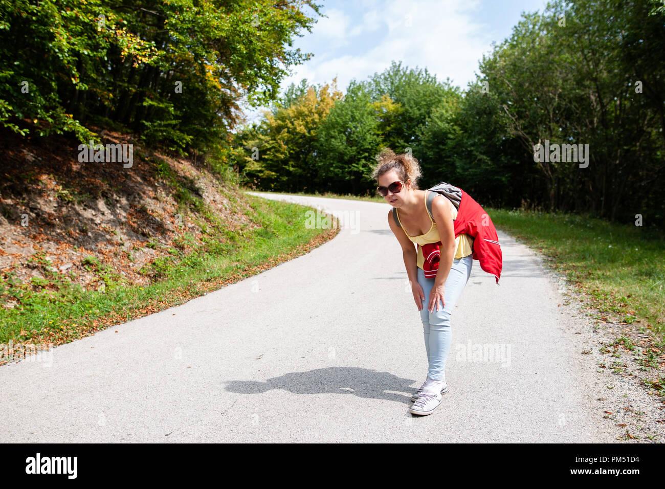 Mujer del viajero cansado y le dolían las piernas de la pérdida de su camino en el bosque en verano Imagen De Stock
