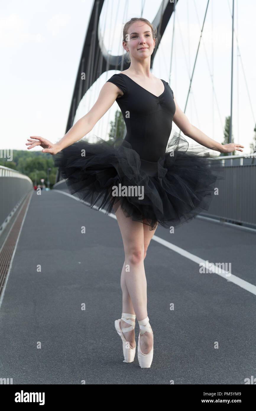 5b600f8d01 Bailarina de ballet bailando en carretera. Disparo de longitud completa. Al  frente.