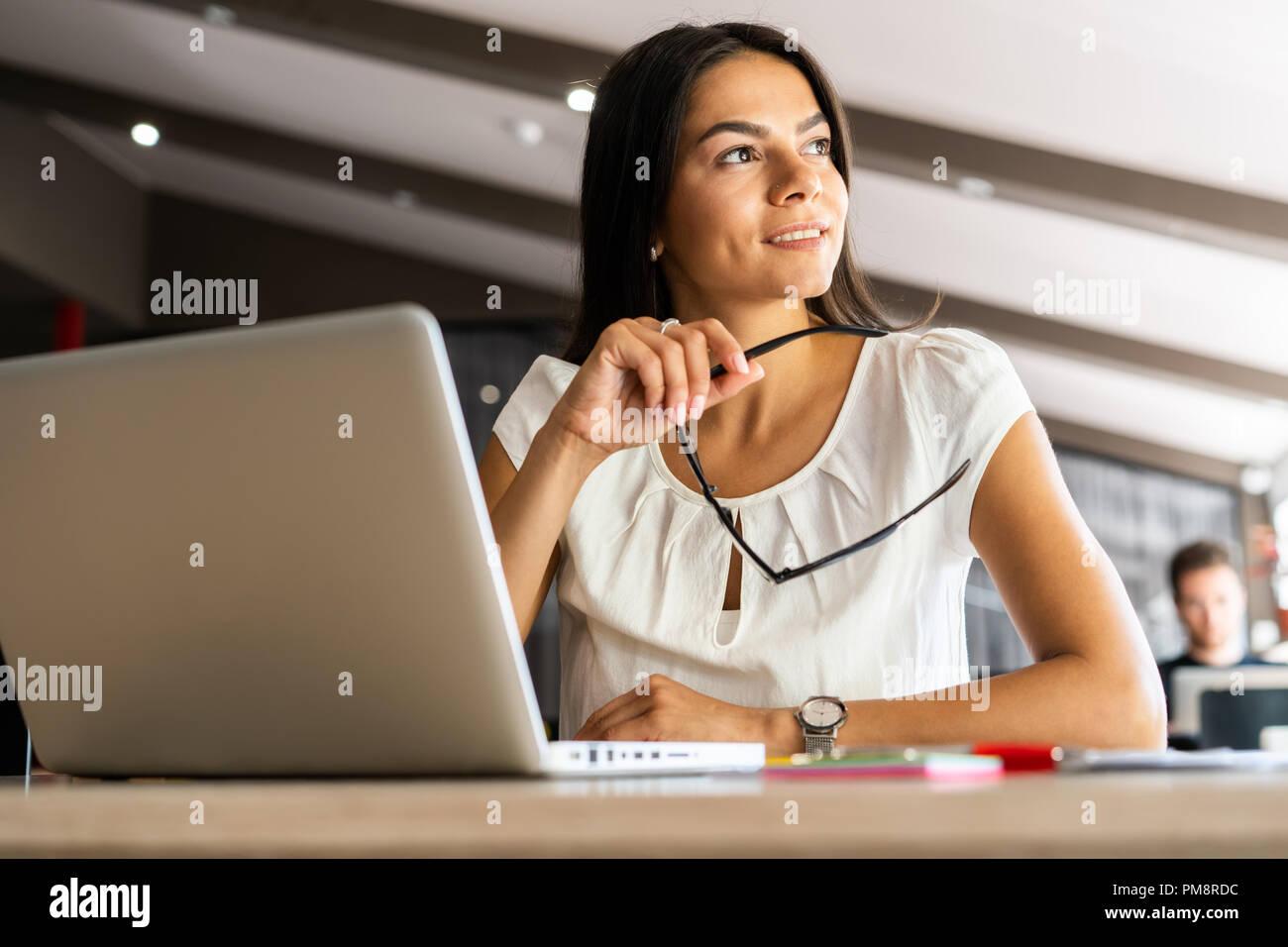 Solución nueva cada día. Seguro joven en smart ropa casual trabajando en el portátil mientras está sentado en su lugar de trabajo en la oficina Imagen De Stock