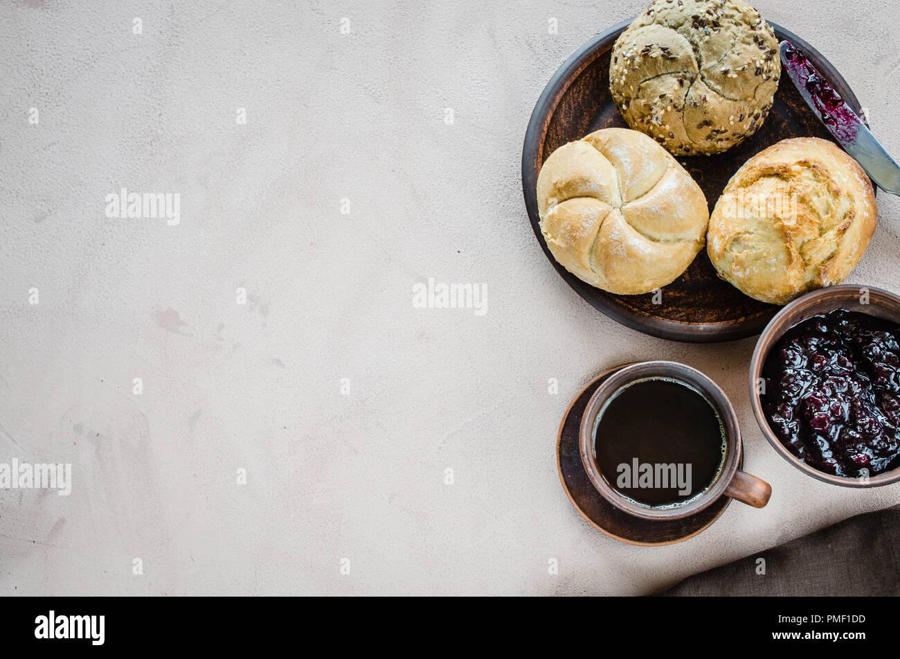 Café americano, bollos frescos y mermelada. Simple desayuno en la mañana. Estilo rústico. Imagen De Stock