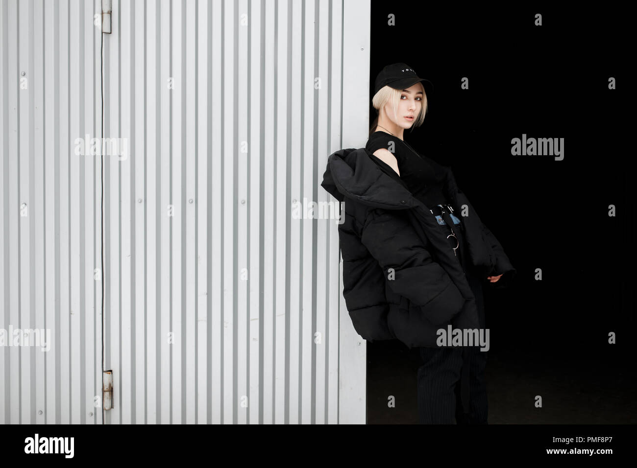 a7c29502be742c Hermosa chica de moda en un elegante negro con un capuchón negro chaqueta  de moda posando