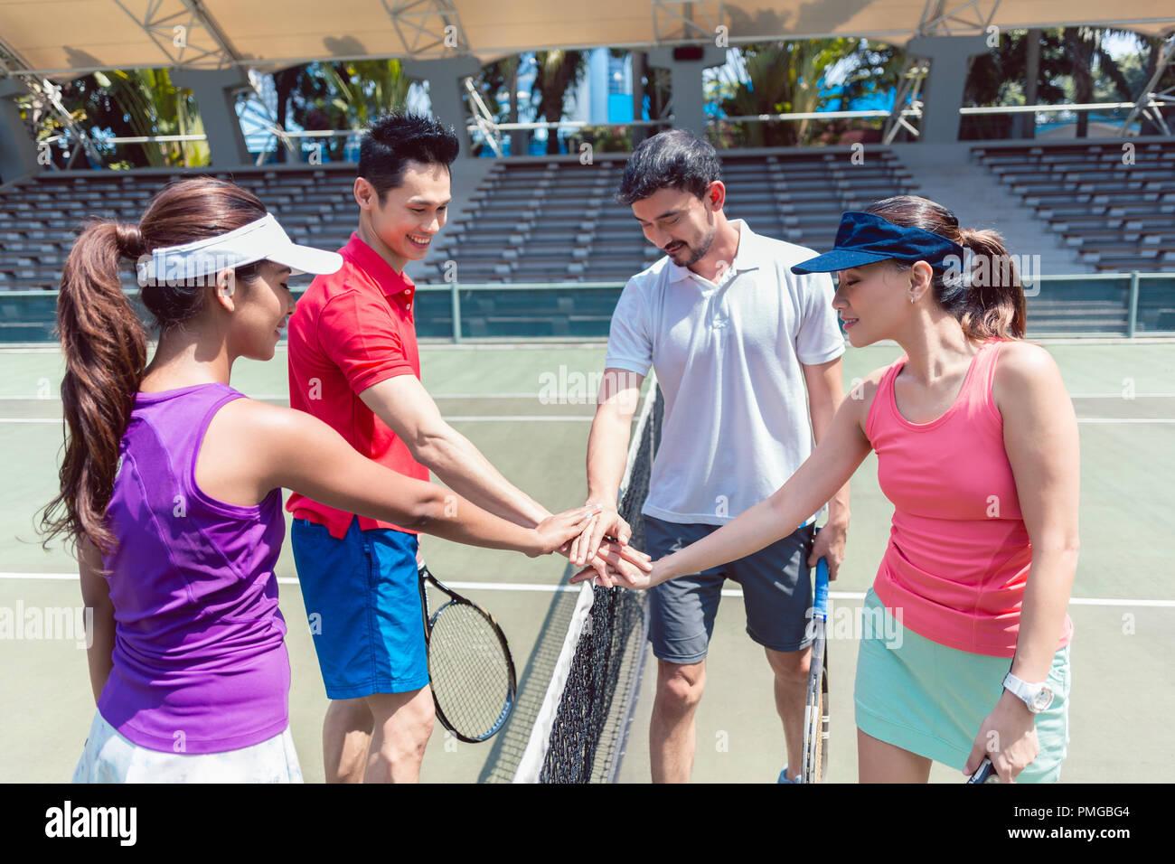 Cuatro jóvenes tenistas poniendo las manos juntas antes del match mixtos dobles Foto de stock