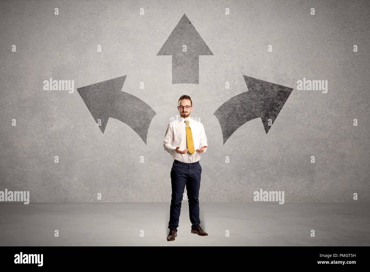 Encantador empresario en duda, eligiendo desde tres direcciones en frente de una pared gris Imagen De Stock