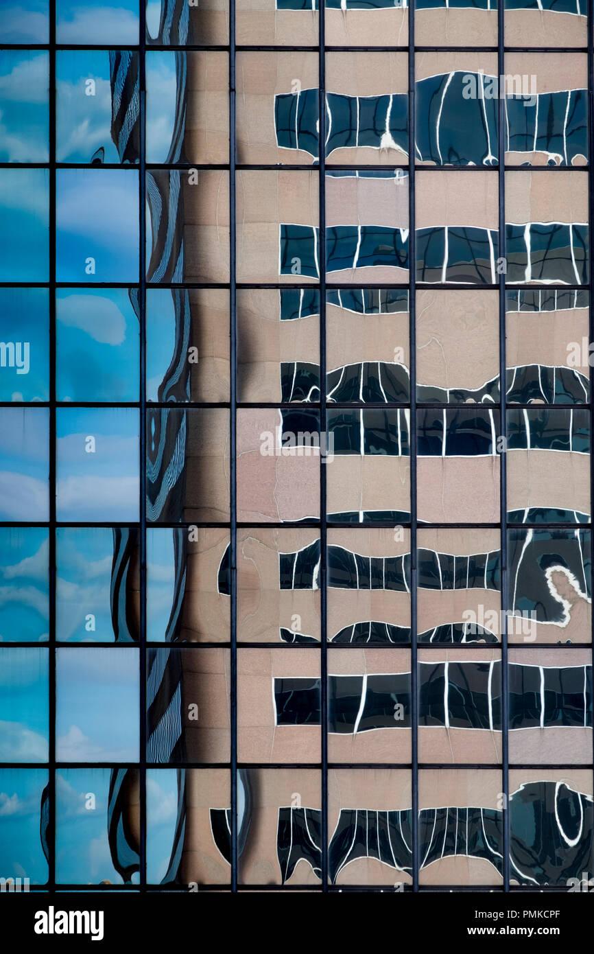 Detalle de la arquitectura en el bloque de oficinas, Birmingham, Alabama. Un reflejo distorsionado de un bloque de oficinas en las ventanas reflectantes de otro bloque de oficinas. Imagen De Stock