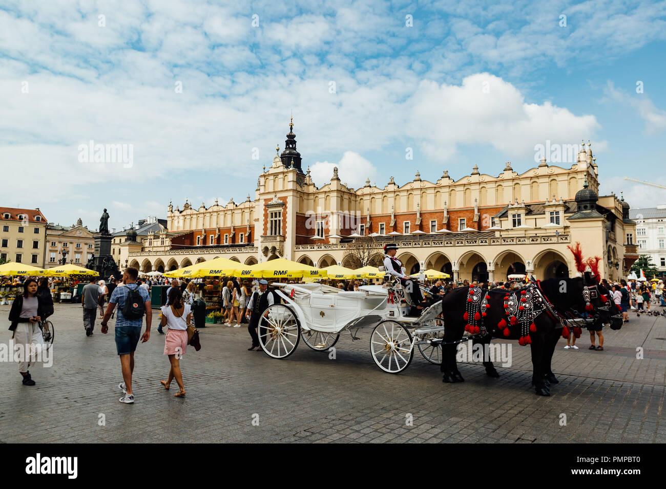Cracovia, Polonia - Agosto 15th, 2018: Tradicional de caballos esperando a los pasajeros en la parte delantera de la tela Hall en la principal plaza del mercado de Cracovia. Foto de stock