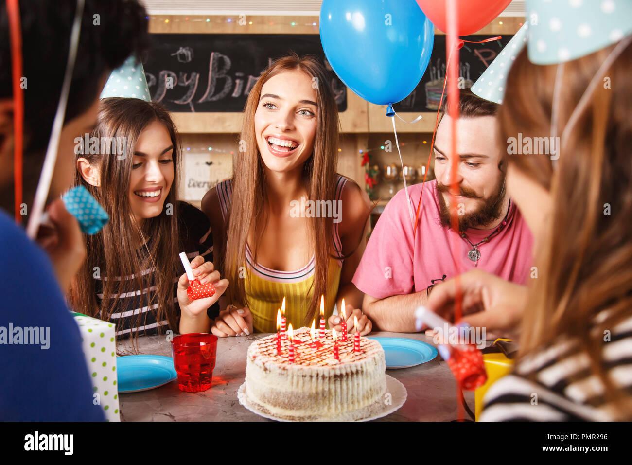 Cinco jóvenes adultos celebrando una fiesta de cumpleaños como ellos sentados alrededor de una mesa con tortas y gorros de fiesta Imagen De Stock