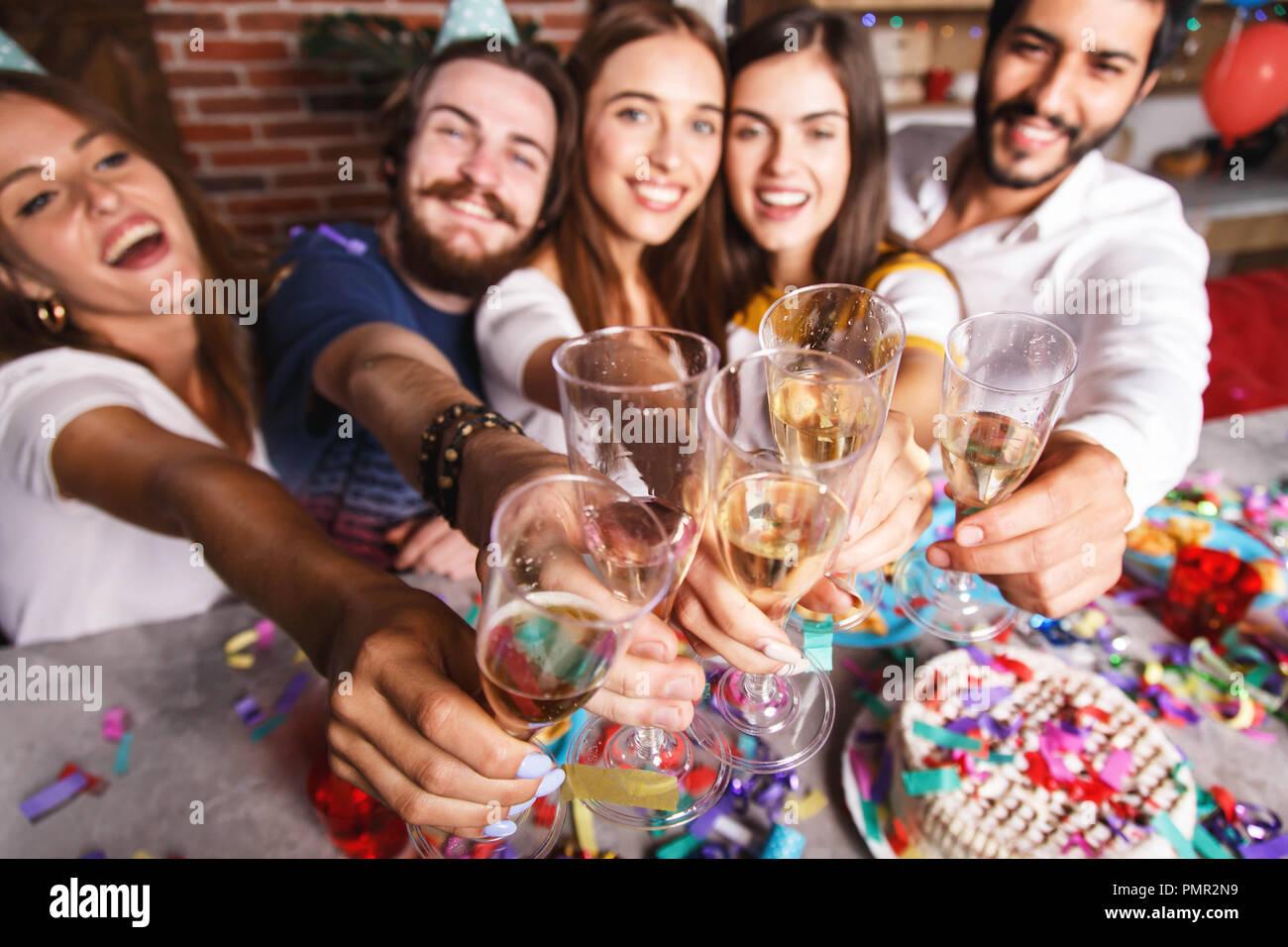 Atractivo multicultural mejores amigos riendo y elevando los vasos con champán, celebrando la fiesta de cumpleaños Foto de stock