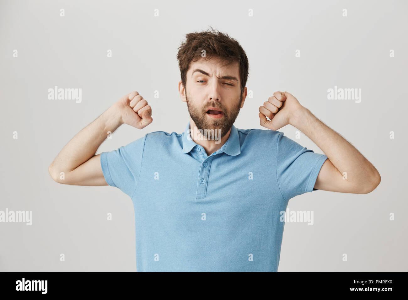 Desordenado y soñolienta adulto hombre barbado estiramientos con manos levantadas y bostezos, entrecerrar como si él desperté, erguido sobre un fondo gris. El hombre se levantó y permanecer en el baño para lavarse la cara Imagen De Stock