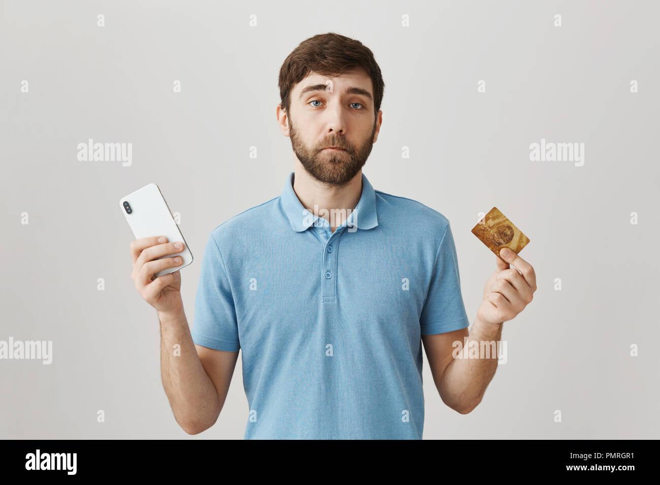 Inútil tarjeta de crédito con saldo insuficiente. Sombrío retrato del joven barbudo disgustó guy celebración smartphone y tarjeta bancaria, teniendo problemas con el pago en línea, erguido sobre fondo gris Foto de stock