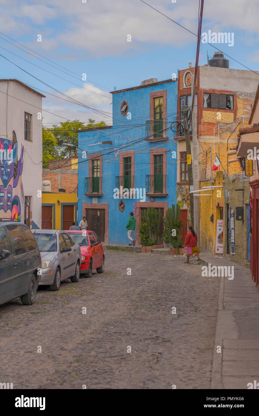 Encantadora calle adoquinada, con algunos coches, peatones y una gran casa azul, en San Miguel de Allende, México Imagen De Stock