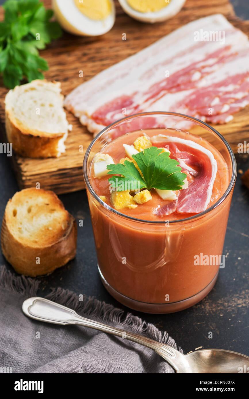 Español tradicional sopa crema de tomate andaluz salmorejo servido en un vaso con jamón y huevo Imagen De Stock