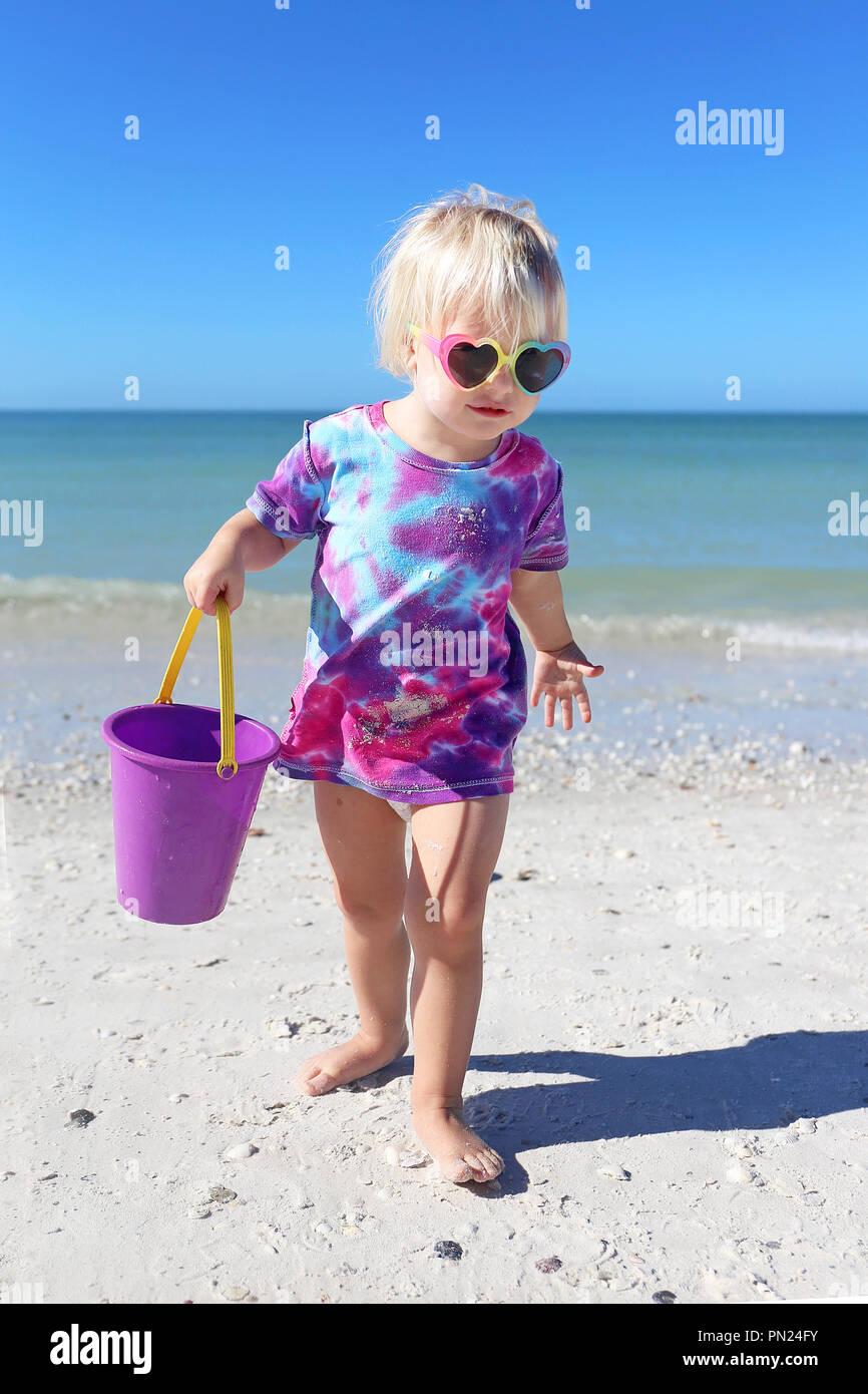 1d9fc2a7bf Un pequeño y lindo niño de 2 años es niña jugando en la playa por el  océano, la recolección de conchas en la arena en su cubo.