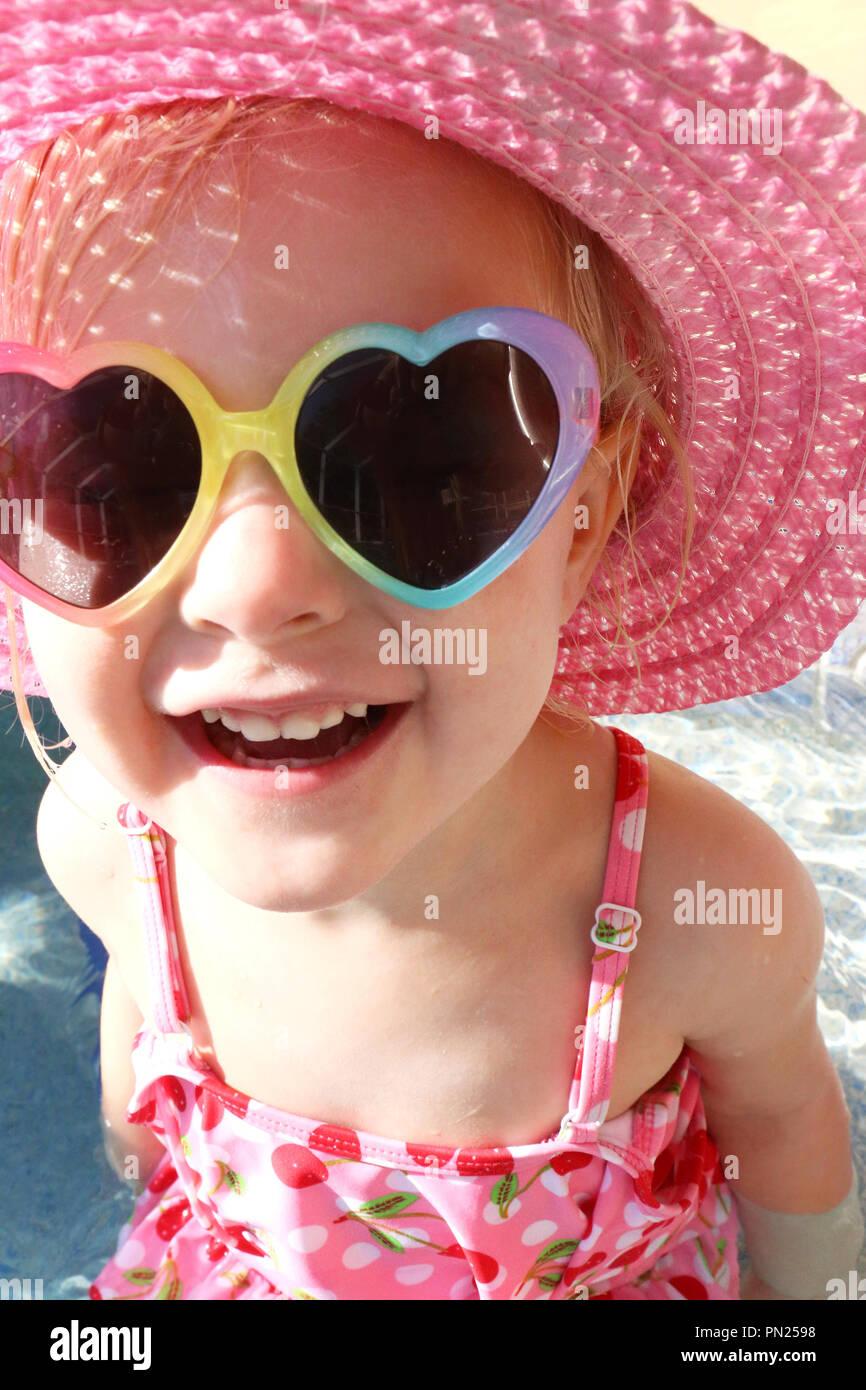 7c58ddc472 Un pequeño y lindo niño niña de 2 años está sentado fuera en la piscina en