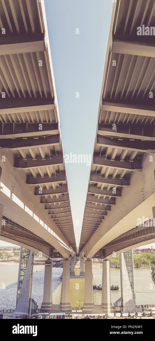 Vista bajo el nuevo puente moderno. Autopista que conduce al otro lado del río Foto de stock