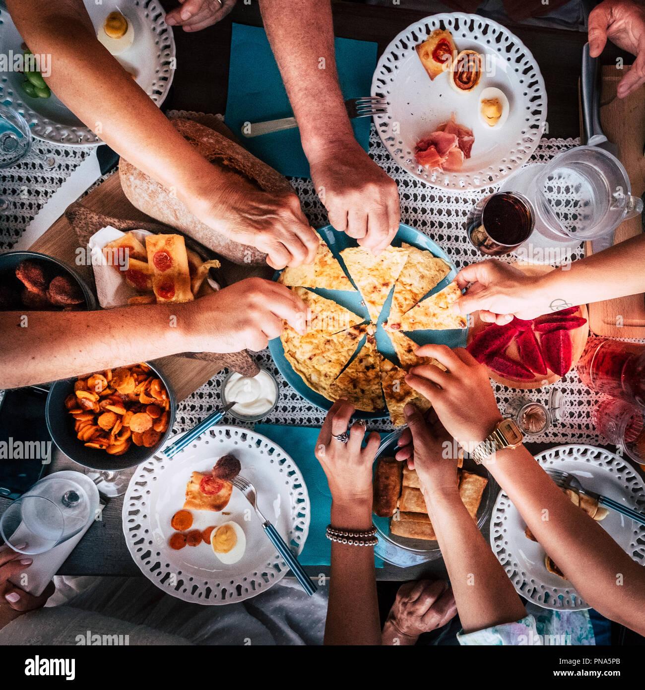 Vista aérea desde la parte superior de la tabla y las manos y un montón de comida y bebidas. Celebración y party concepto imagen. Todas las manos tomando de la misma pla Imagen De Stock