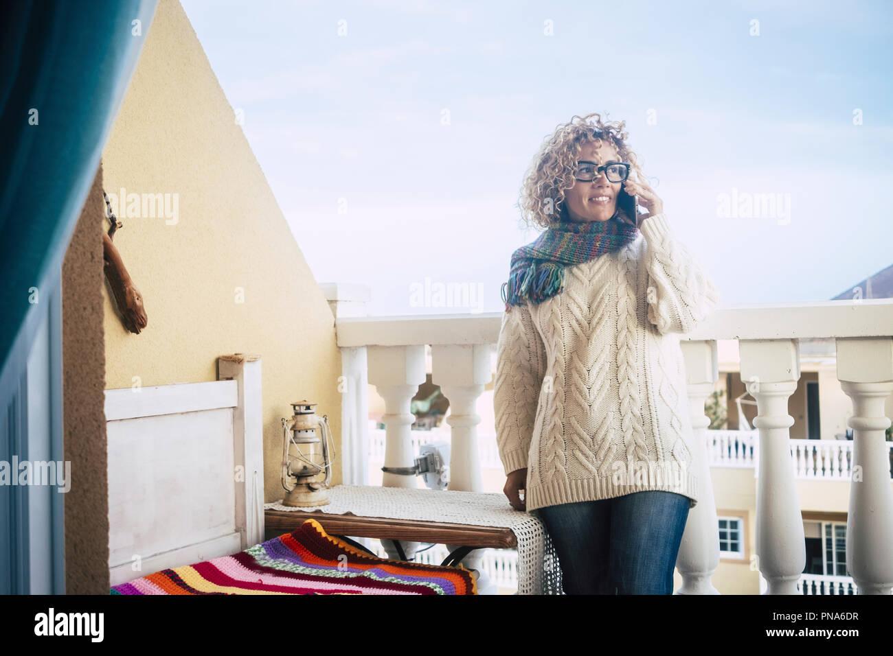 Hermosa mujer caucásica sonrisa mientras trabajo en casa en la terraza al aire libre con un ordenador portátil y un teléfono móvil. Permanezca conectado y trabaje fuera de la oficina s Imagen De Stock
