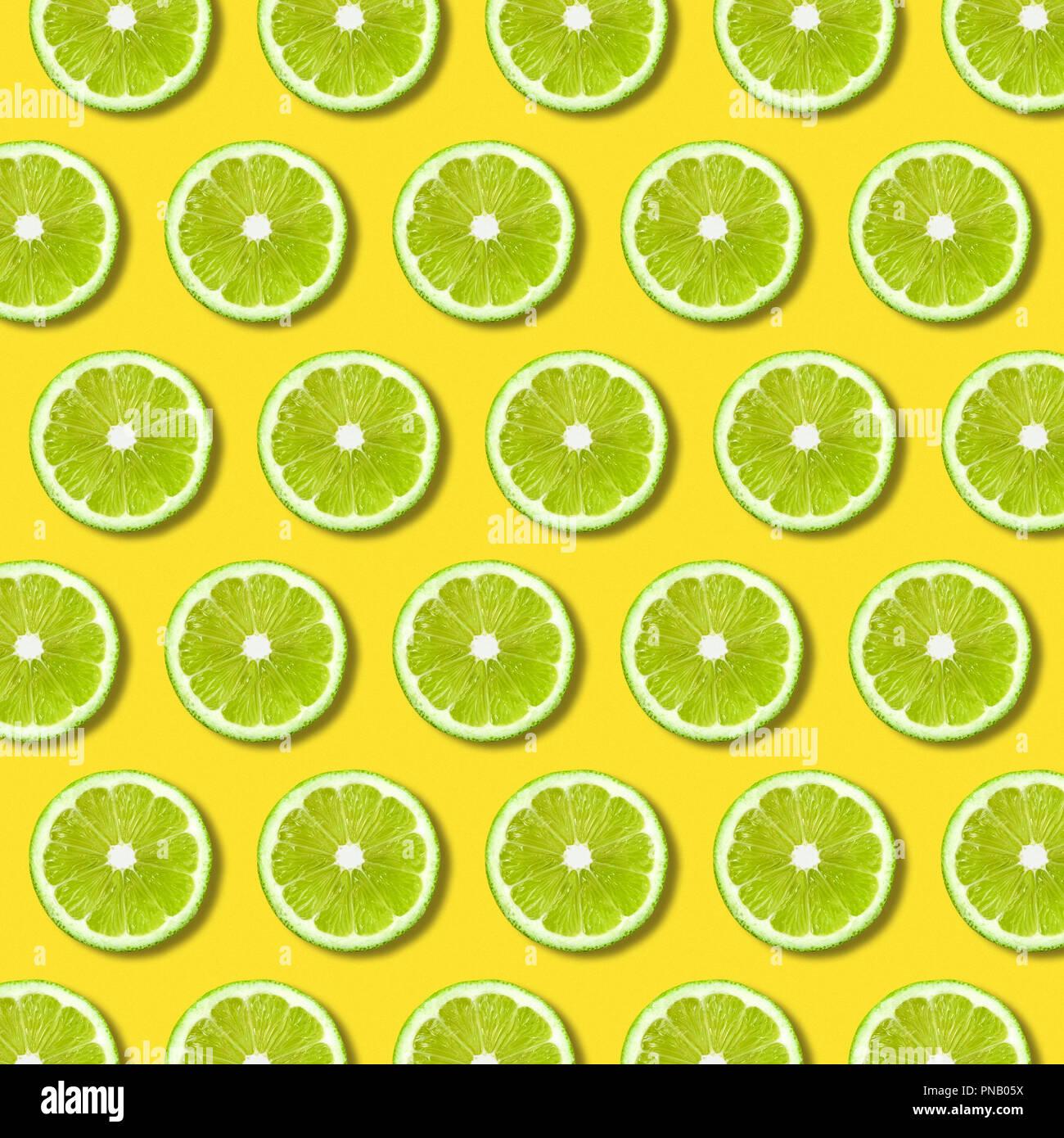 Rodajas de limón verde patrón sobre fondo de color amarillo vibrante. Textura Alimentos laicos fija mínima Imagen De Stock