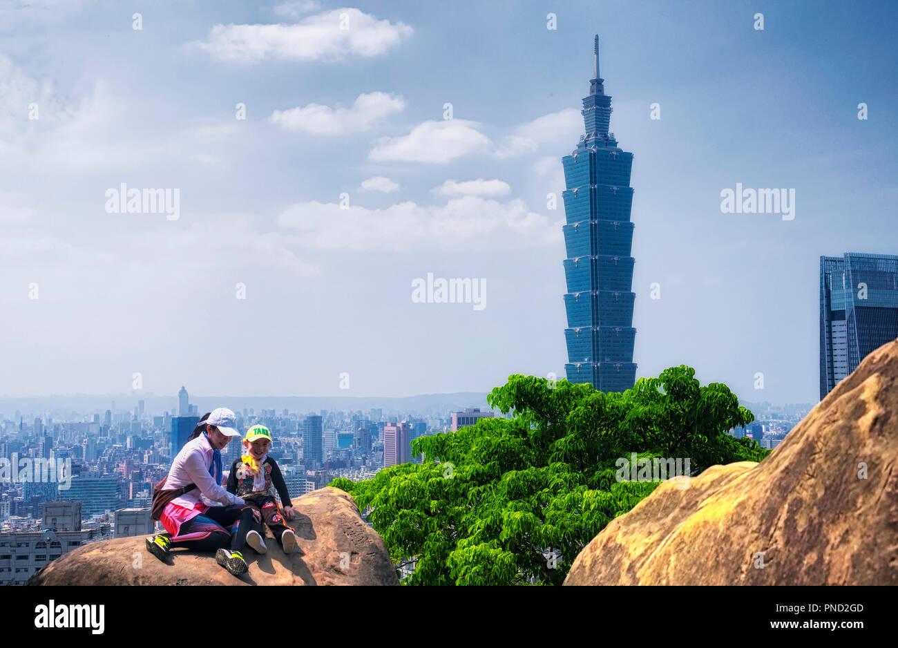 El 1 de abril de 2018. Taipei, Taiwán. Una madre y su hija posando en las rocas con el emblemático edificio Taipei 101 elevándose sobre arquitectura genérica en la ciudad Imagen De Stock
