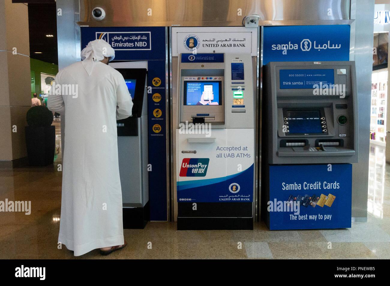 Los Emiratos hombre utilizando dinero en efectivo en cajeros automáticos en Dubai, Emiratos Árabes Unidos Imagen De Stock
