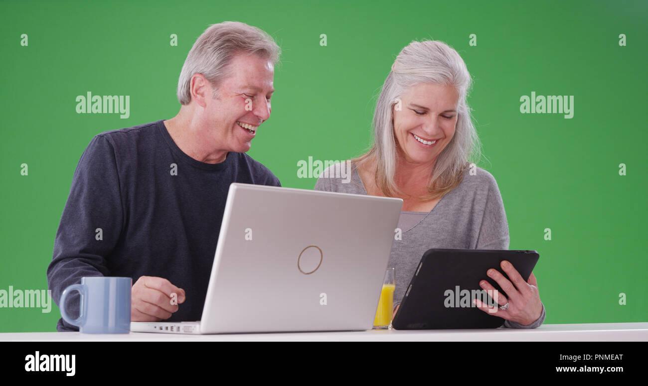 Retrato de un encantador casco blanco pareja utilizando dispositivos inalámbricos en verde Foto de stock