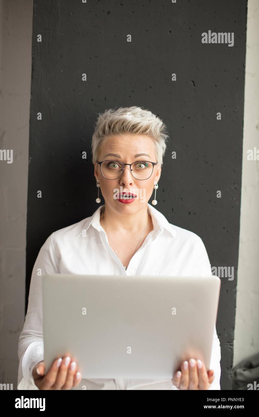 Sorprendido mujer leyendo información inesperada en la laptop con la boca abierta y los ojos saltones Foto de stock
