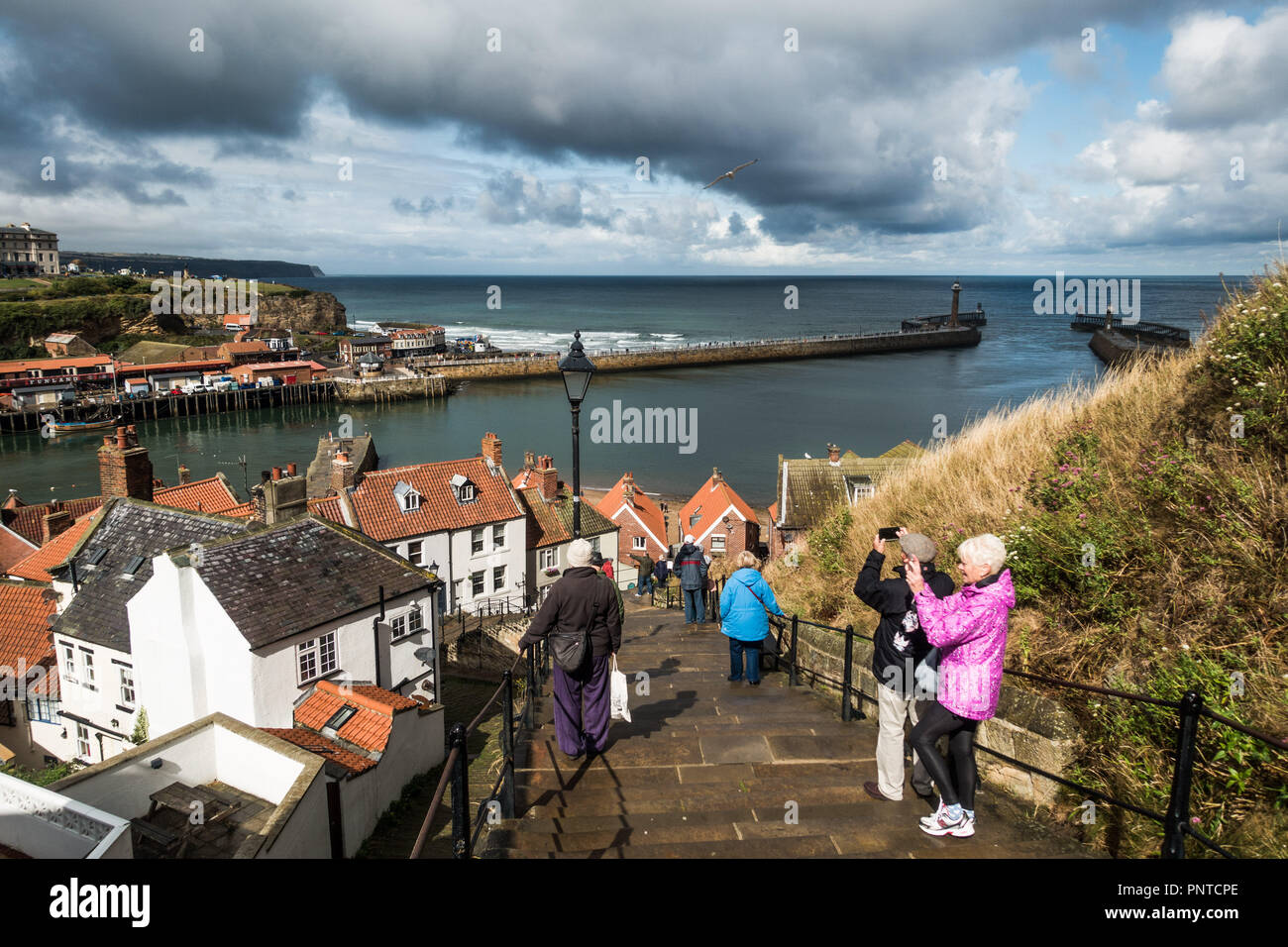 Los pasos hasta la abadía y vista de la entrada del puerto en Whitby, Yorkshire con amenaza de lluvia Imagen De Stock