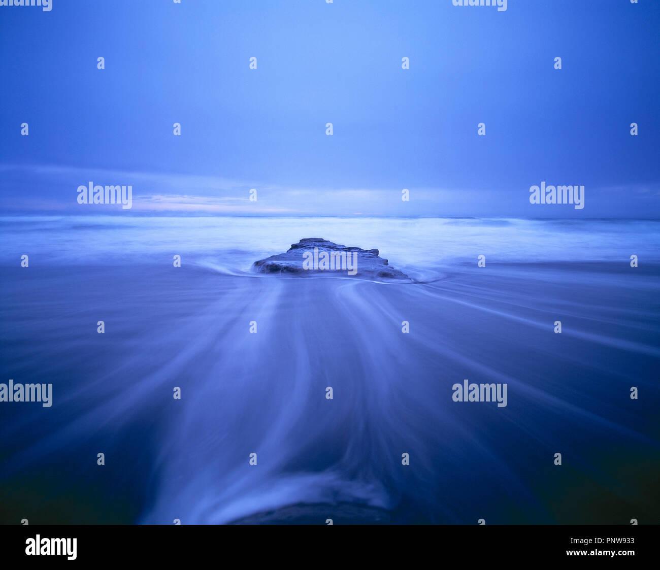 Nueva Zelandia. El norte de la isla. Costa. Azul atmosférica cerca de marejada agua arremolinándose alrededor del rock. Imagen De Stock