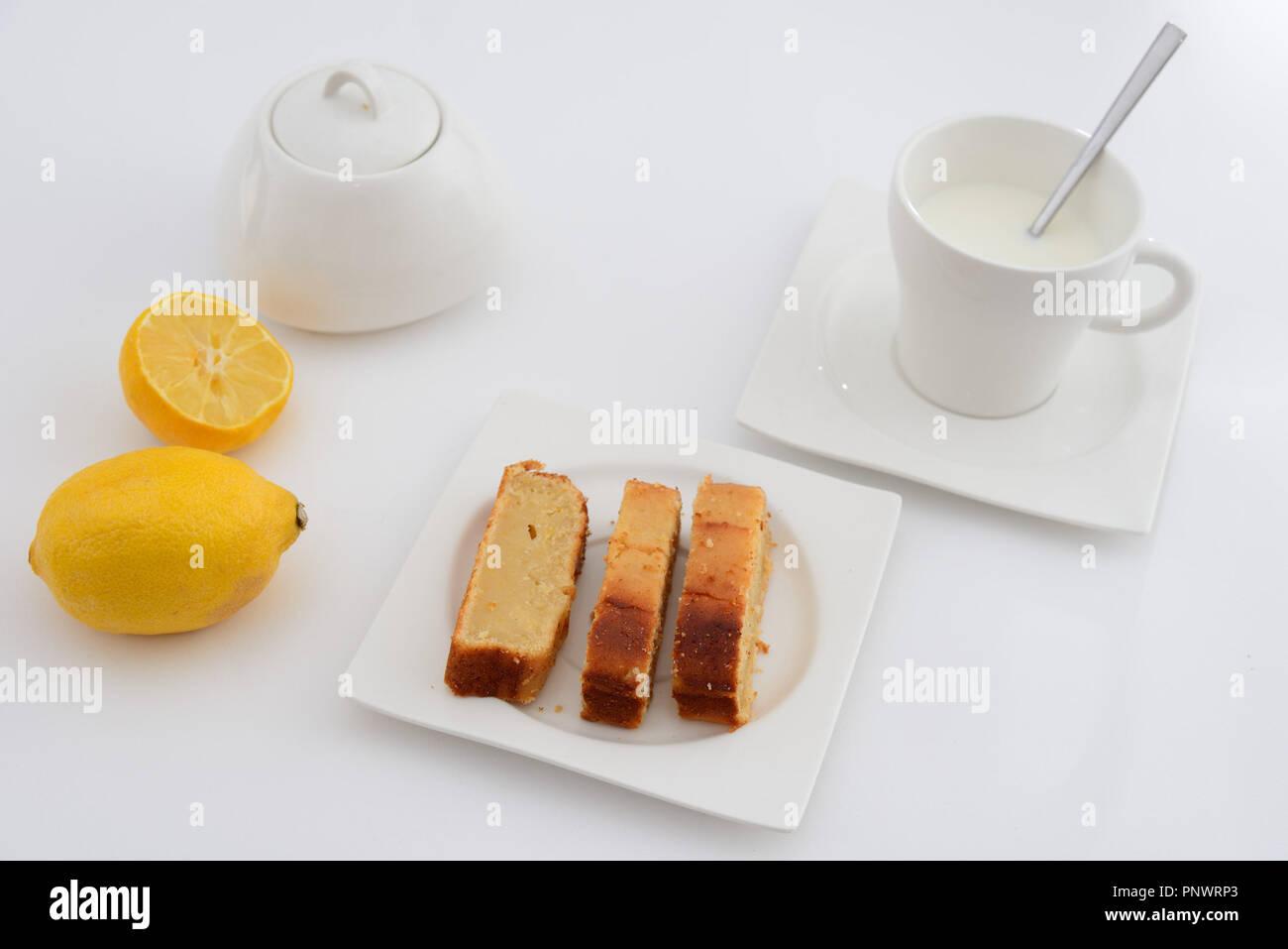 Desayuno. Taza con leche y bizcocho de limón en un plato. Fondo blanco Imagen De Stock