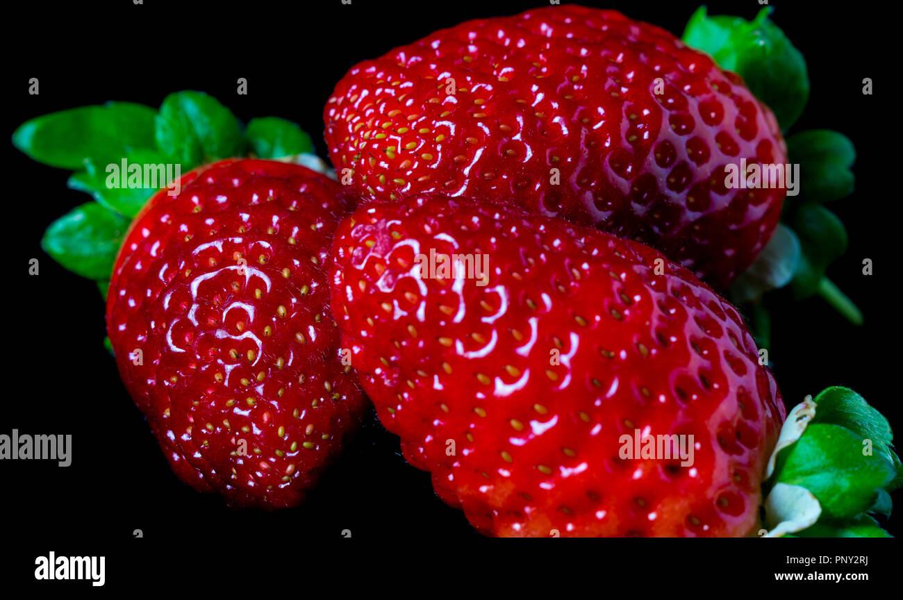 Close Up De Tres Fresas Frescas Sobre Un Fondo Negro útiles