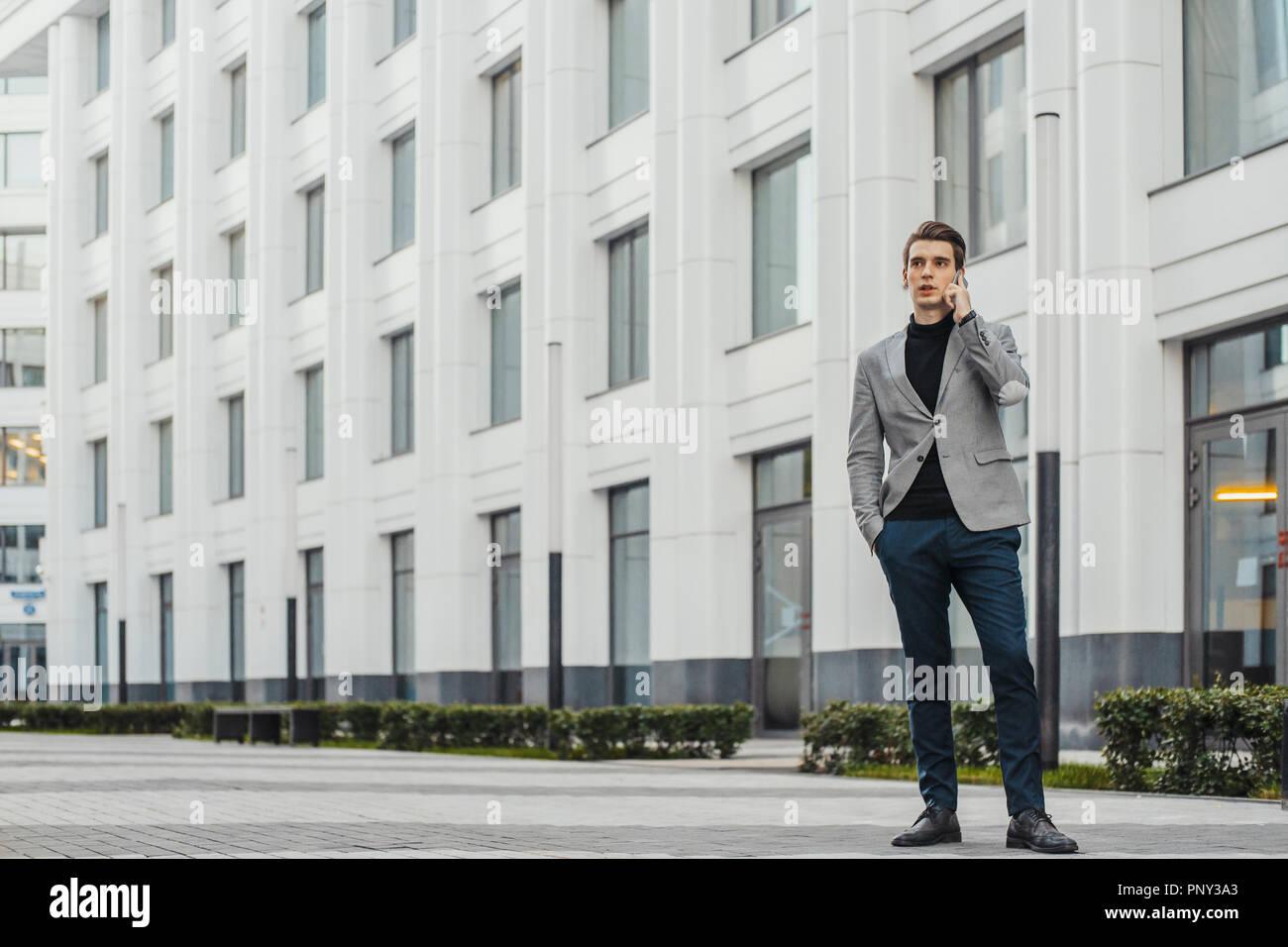 Joven empresario hablando por teléfono móvil situado junto al centro de negocios. Imagen De Stock