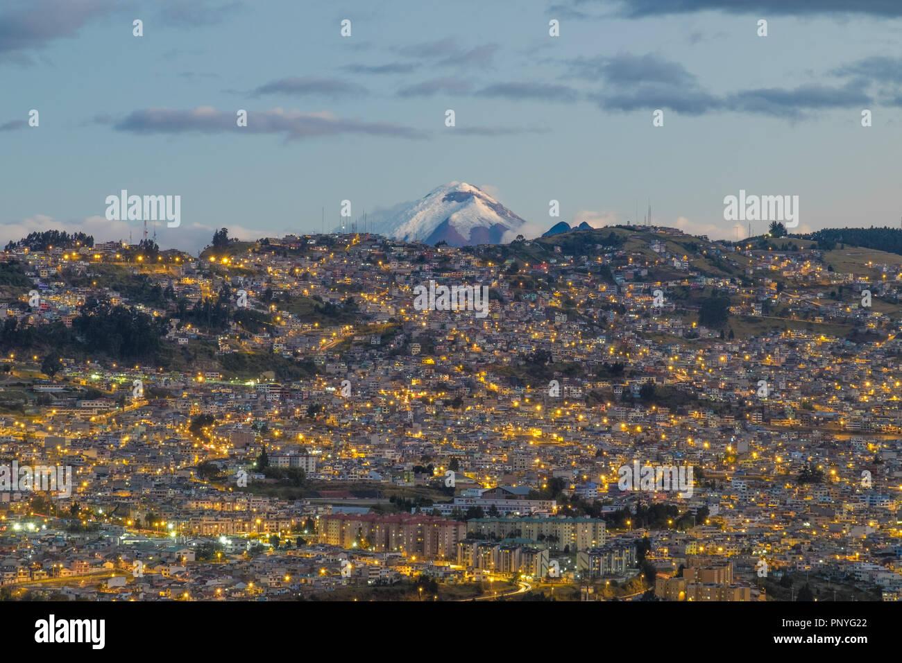 Vista de Quito en la noche y en el fondo del volcán Cotopaxi, Ecuador Imagen De Stock