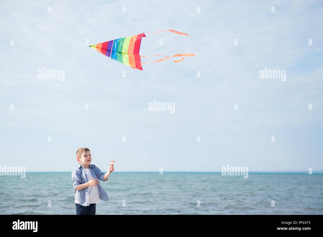 Poco feliz muchacho caucásico con la habilidad de volar cometas multicolores en el horizonte del mar antecedentes Foto de stock