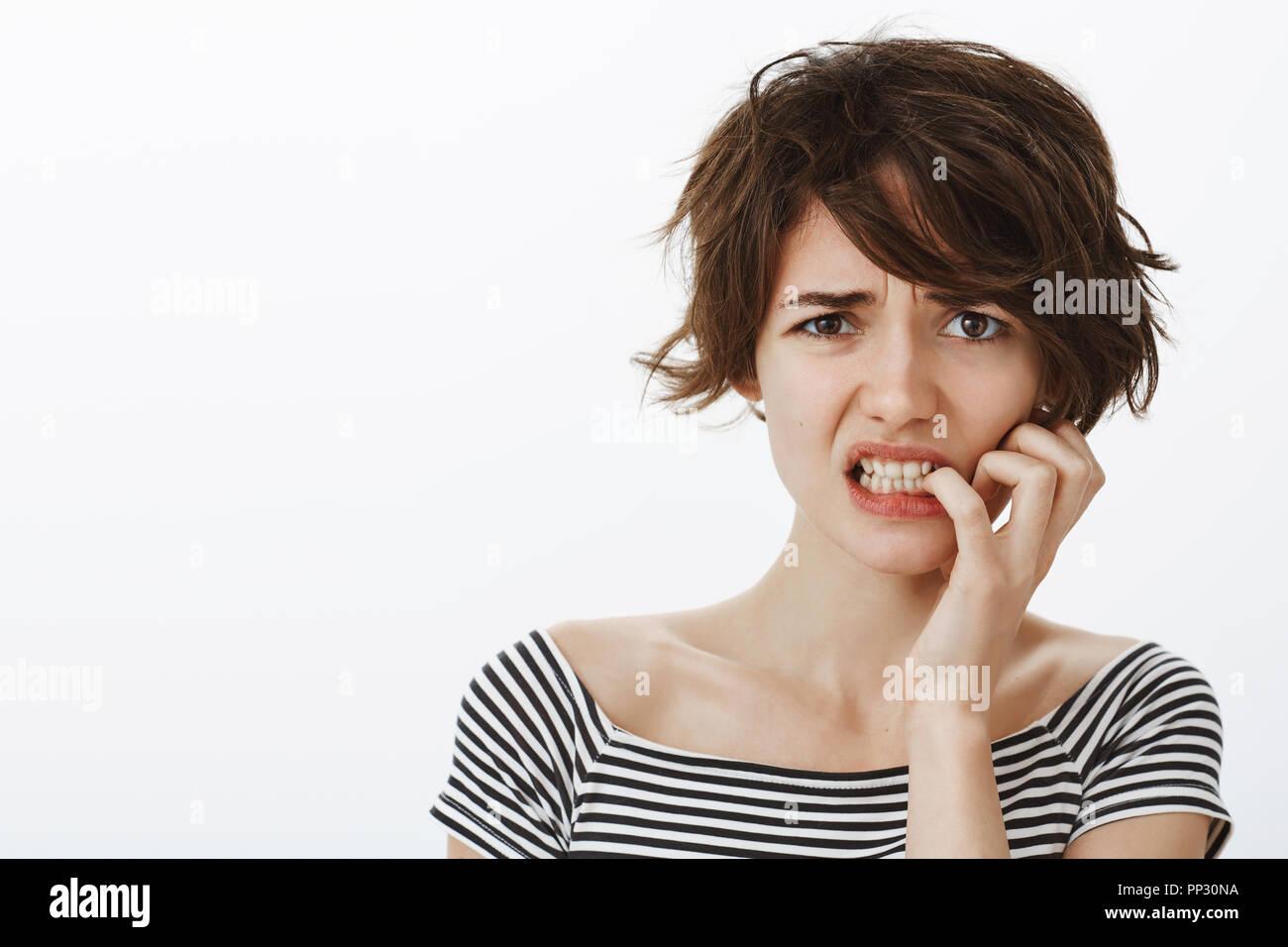Chica suggesring de ansiedad y una reacción exagerada. Retrato de preocupados intensa novia con corta el pelo desordenado, fruncir el ceño y mordiendo las uñas mientras se sentía nervioso, ser molestado por pensamientos Imagen De Stock