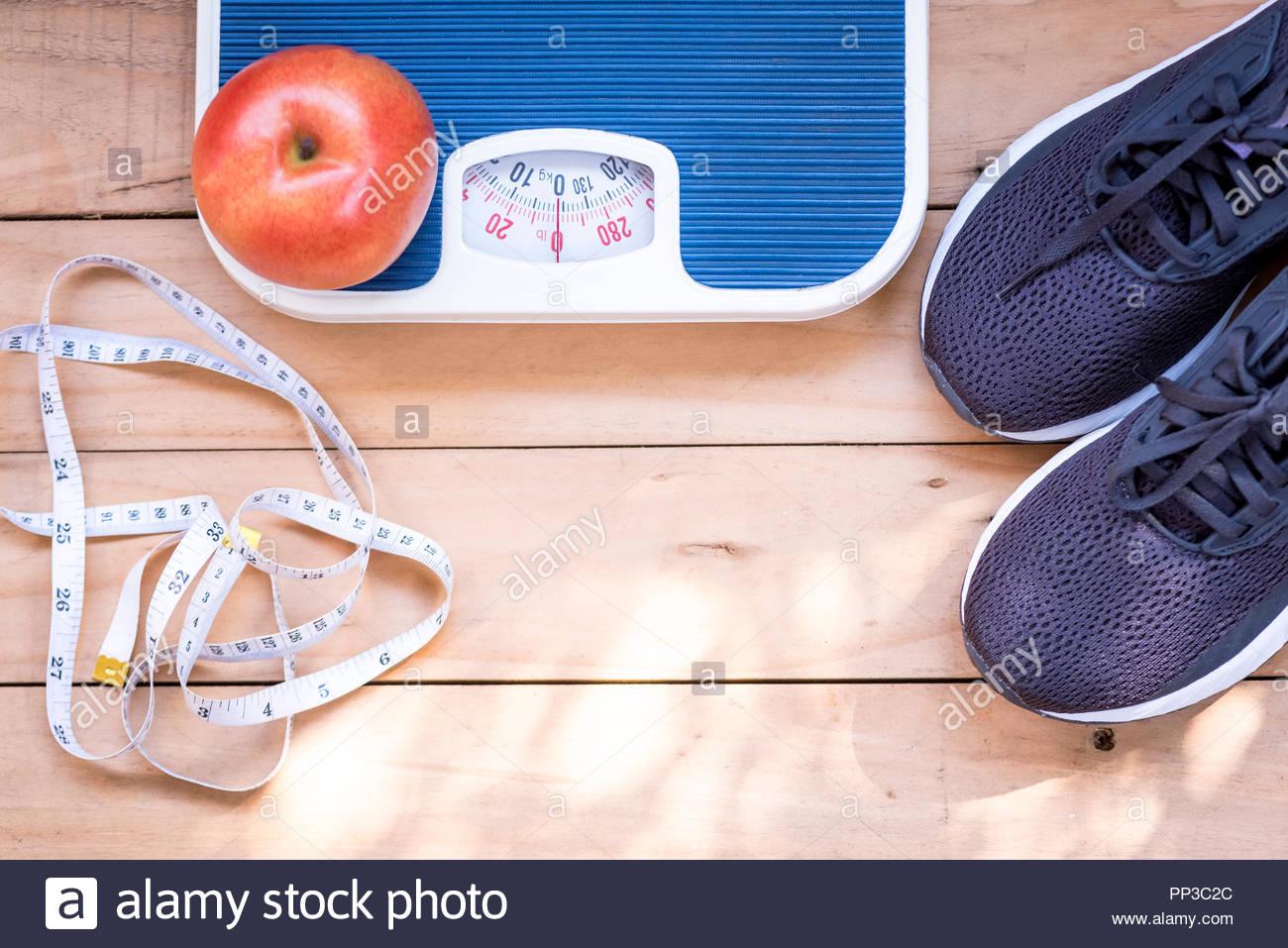 Zapatillas negras , manzana roja, blanca cinta de medir y básculas en el piso de madera. Accesorios deportivos Imagen De Stock