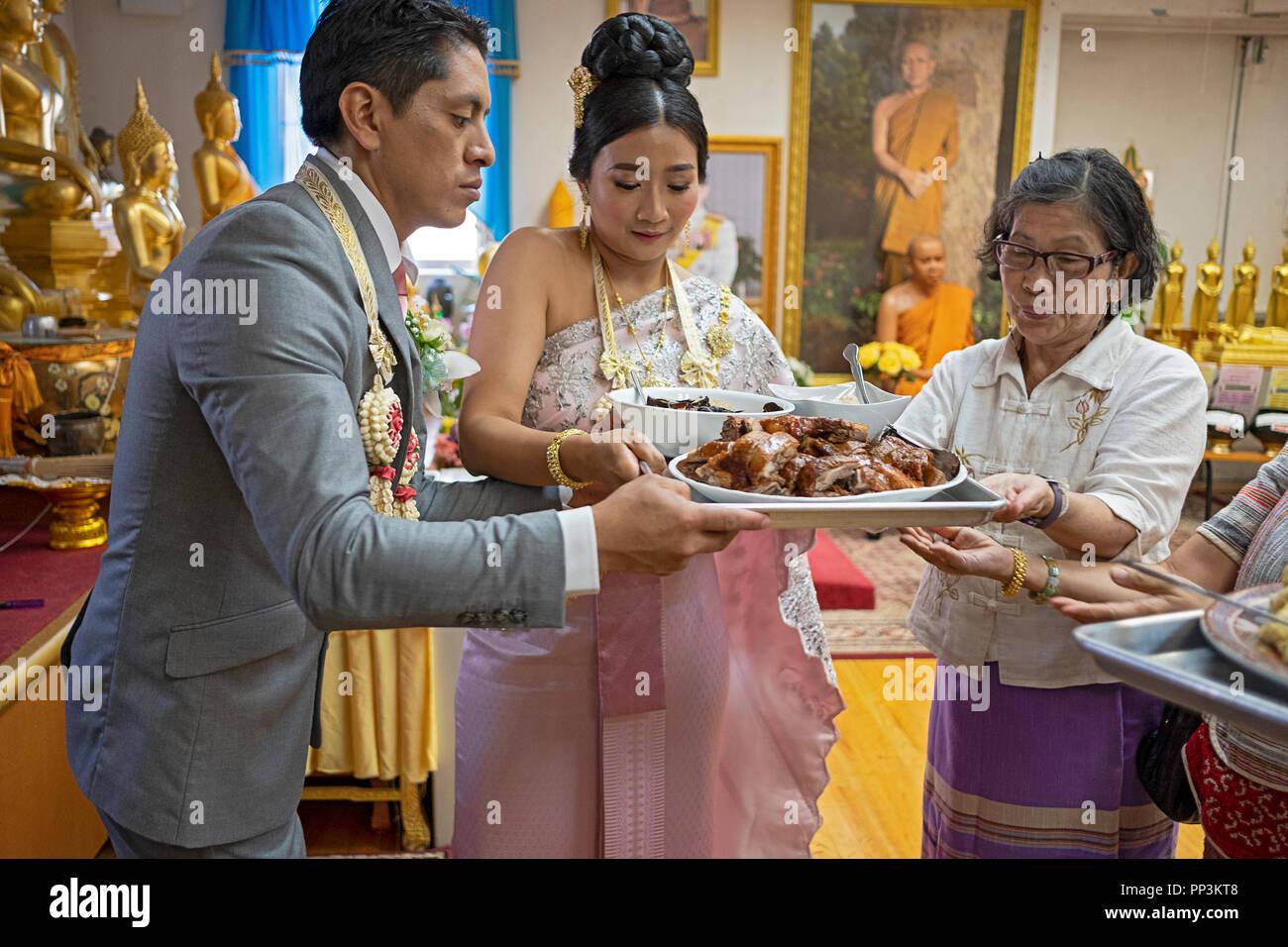 Recién casados en un templo budista participar en la tradición, donde la congregación alimentando a los monjes. En Queens, Nueva York. Imagen De Stock