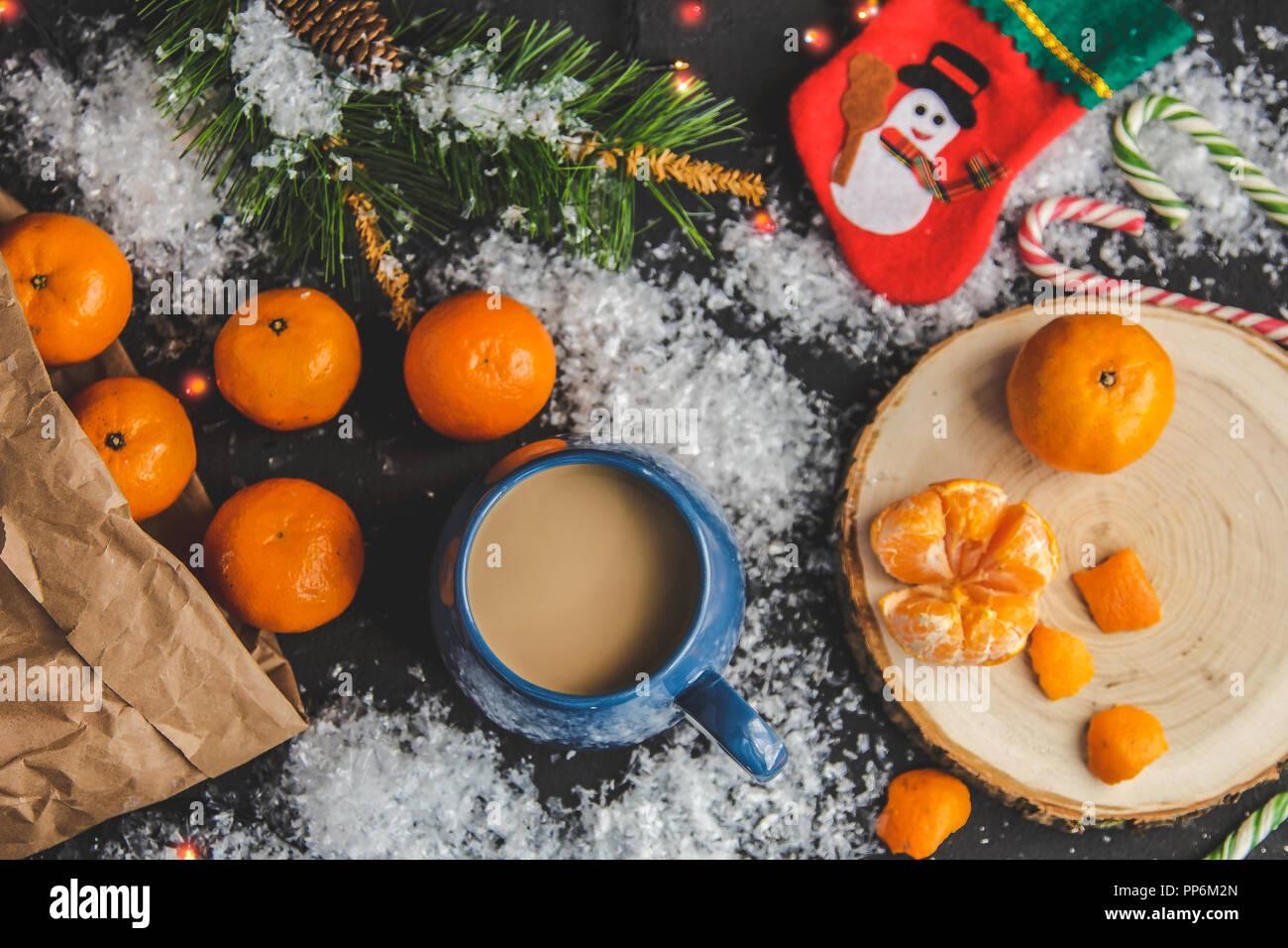 Navidad y Año Nuevo concepto. Las mandarinas, taza de café, la nieve, la rama del árbol de Navidad. Contra un fondo oscuro. Vista superior de laicos plana Imagen De Stock