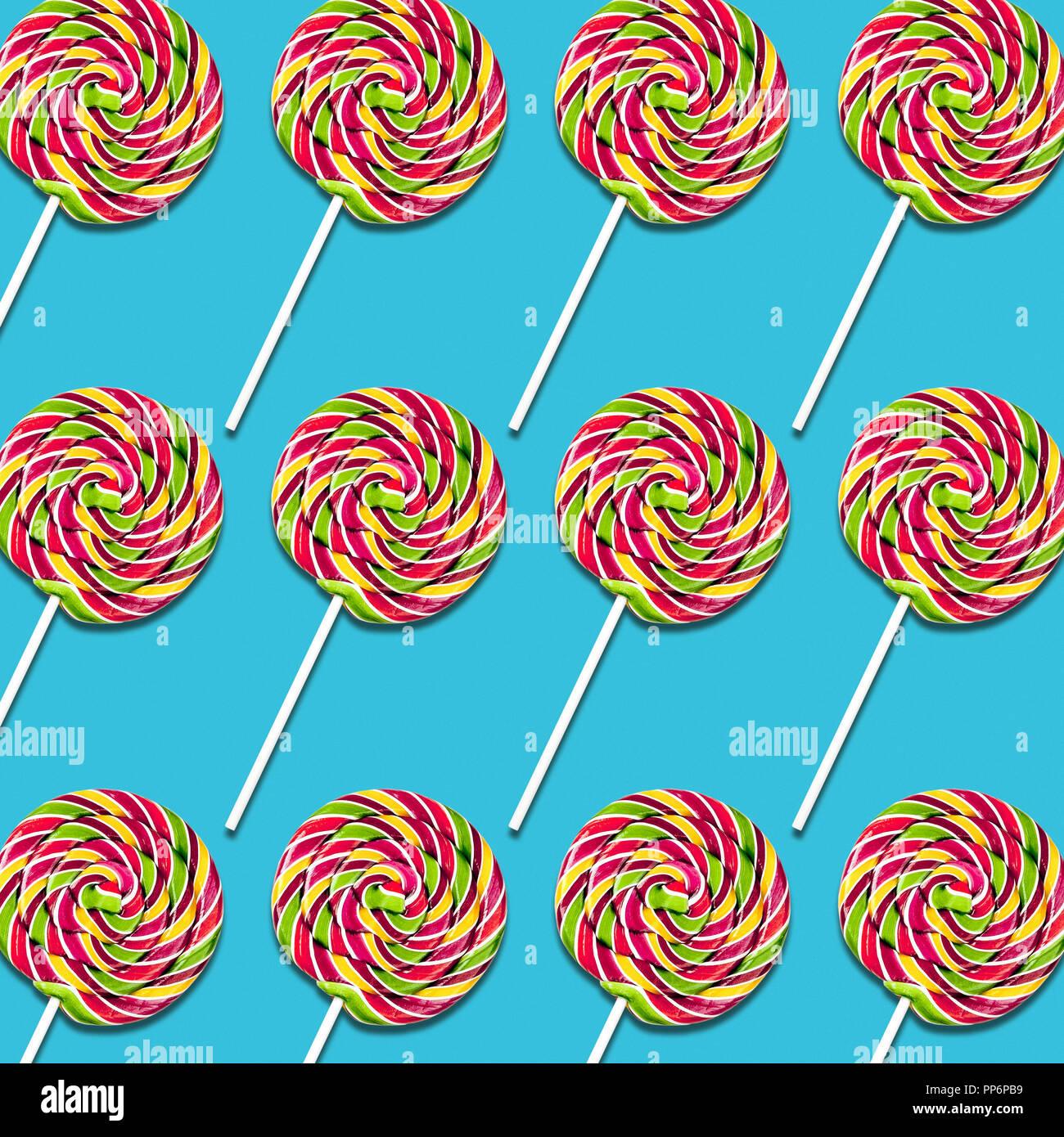 Disposición simétrica de lollipop caramelos sobre fondo turquesa, coloridos dulces de textura de alimentos Foto de stock