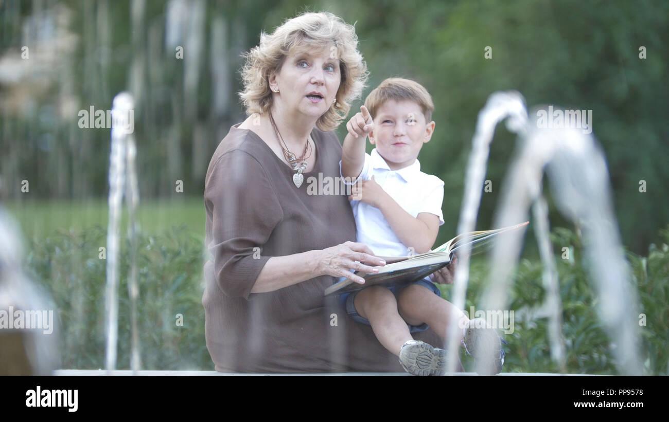 Abuela con nieto leyendo un libro juntos Imagen De Stock