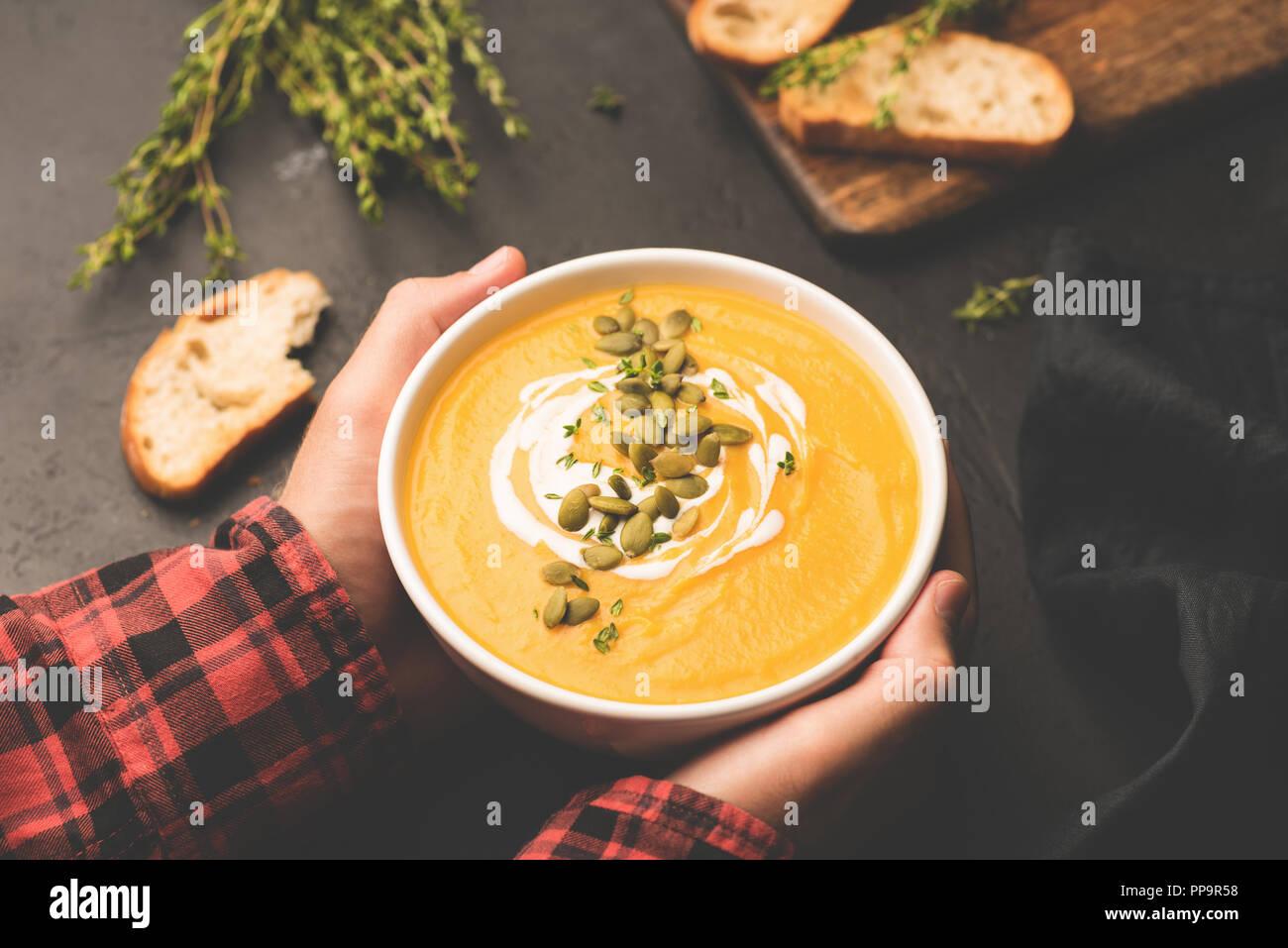 Persona sosteniendo el tazón de sopa de calabaza caliente en las manos. Confort de alimentos, concepto de comida de otoño Imagen De Stock