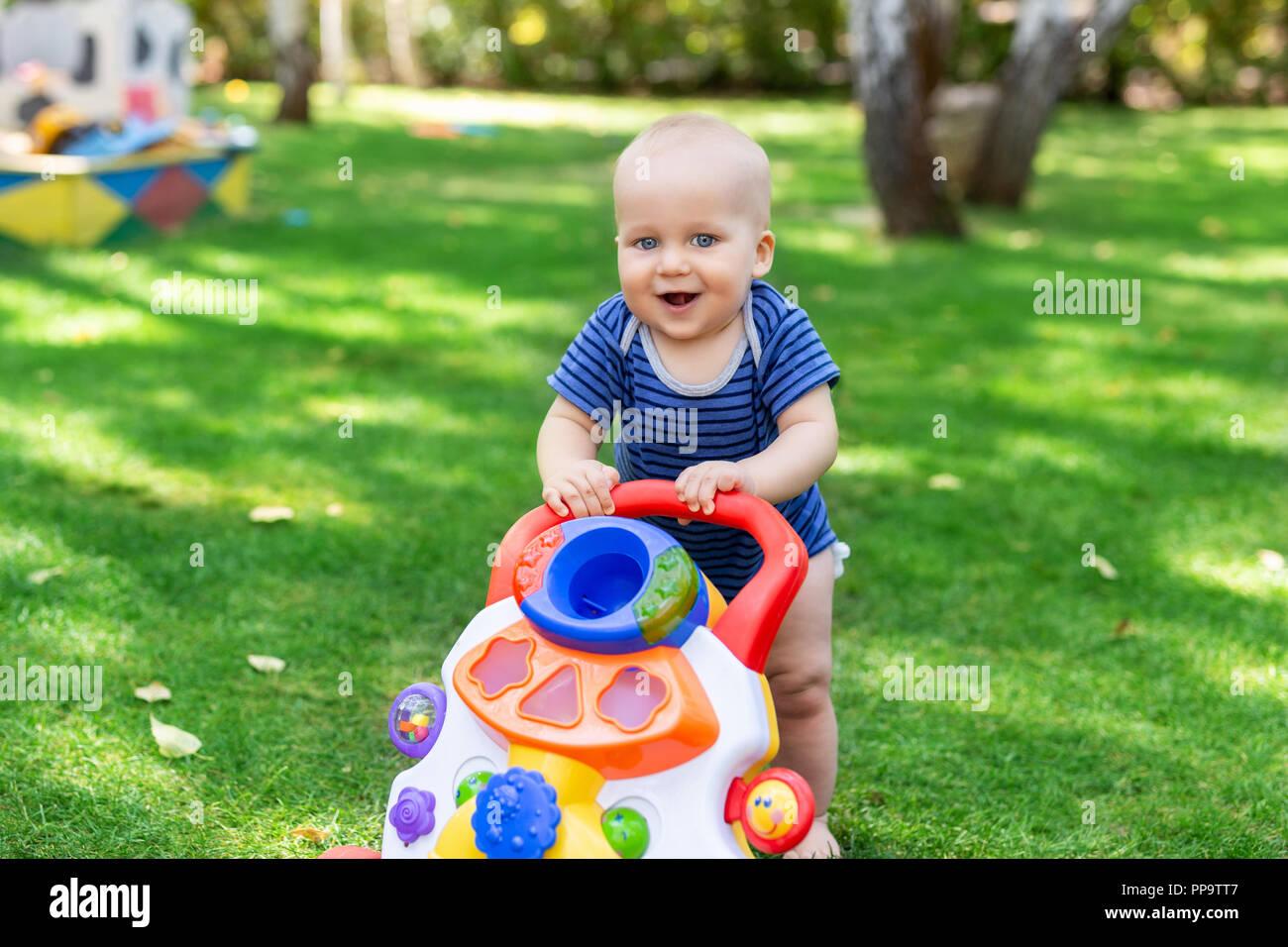 Cute little boy aprendiendo a caminar con andador toy en el verde césped en el patio. Bebé riendo y divirtiéndose haciendo primer paso al parque en día soleado en el exterior. Infancia feliz concepto Imagen De Stock